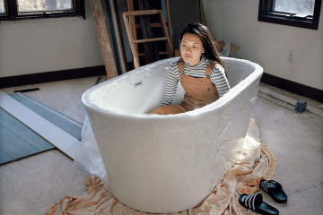 """artist Cici Cheng in a bathtub. """"This photograph is filled with many different emotions. When I see this photograph, I see my past and present, parts of myself that are in conflict with each other, my memories and parts of my identity."""""""