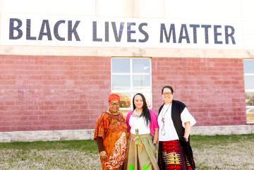 Photo of three black women pastors in front of Black Lives Matter mural
