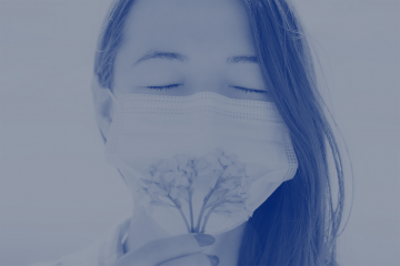 woman sniffing a flower while wearing a mask
