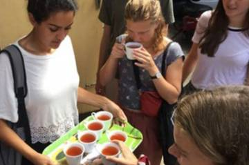Students sample herbal tea at an Ayurvedic hospital