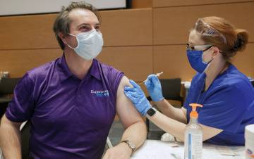 John Yeatts, an internal medicine doctor, left, gets his COVID-19 vaccine from Crystal Adams, a nursing informatics systems specialist at Duke. Photo by Shawn Rocco.