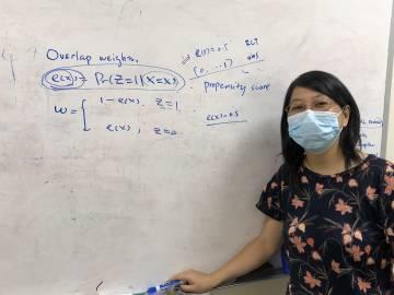 Statistical science professor Fan Li in front of. a whiteboard