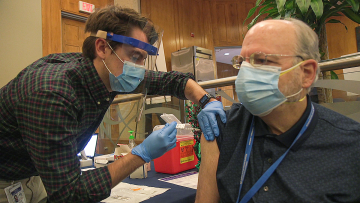 Dr. Barton Haynes receives his first dosage of the COVID vaccine.