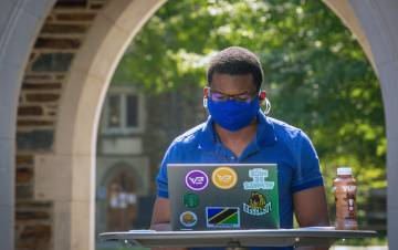 A student on Duke's campus works while wearing a mask. Photo courtesy of University Communications.