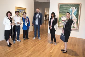 Nasher Museum Director Sarah Schroth leads five visiting cultural preservation experts into the entrance of Wilson Pavilion, pausing in front of paintings by Fernand Léger, Paysage a l'oiseau (left) and Pablo Picasso, Joueur de Flûte et Mangeur de Pastèqu