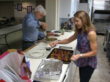 "Instructor Sheri Branson (right) and OLLI member Dr. Mike McLeod prepare for a potluck dinner on May 31, the culmination of the ""What's Cooking"" class, which met at Watts Street Baptist Church."