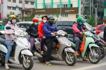 Vietnamese motorcyclists wearing masks
