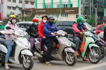 Vietnamese motorcyclists wearing masks